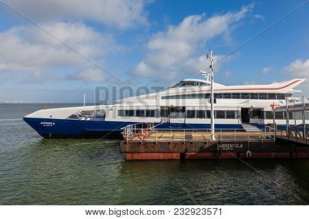 Seixal, Portugal - October 24, 2016: Modern ferry with catamaran hull, waiting for passengers on the Seixal Ferry Terminal to transport the commuters to Lisbon. Built by FBM Marine for Transtejo