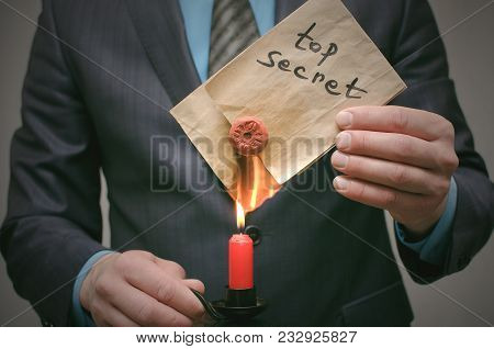 Top Secret Message Concept. A Business Man Burning Secret Documents On Fire. Destruction Of Indicati