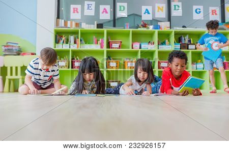 Group Of Diversity Kid Lay Down On Floor And Reading Tale Book In Preschool Library,kindergarten Sch