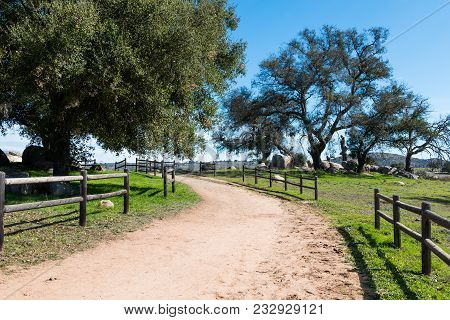 A Dirt Road Lined With A Wooden Fence Turns Toward A Wooded Area With Boulders At Ramona Grasslands