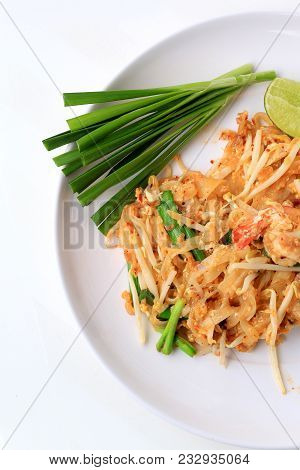 Pad Thai, Stir-fried Rice Noodles With Shrimp In White Plate With Slide Lemon And Green Vegetable. T