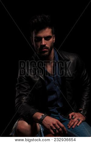seated fashion man in leather jacket resting elbow on knee wearing bracelets and rings, on black background