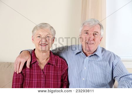 Senior couple sitting together in their living room