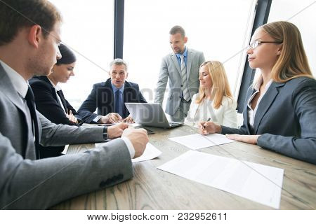Group of business people and lawyers discussing contract papers sitting at the table