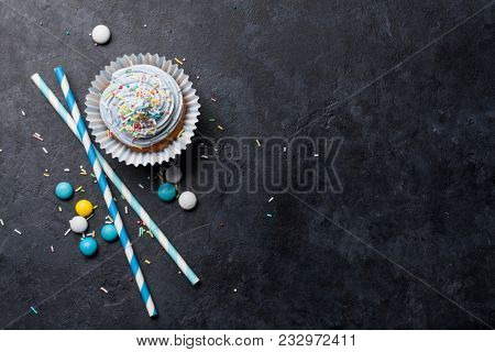Sweet cupcake with colorful decor and candies. Top view with space for your greetings