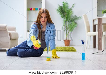 Young woman cleaning floor at home doing chores