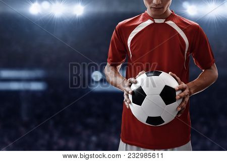 Soccer Player Holding Soccer Ball On The Field