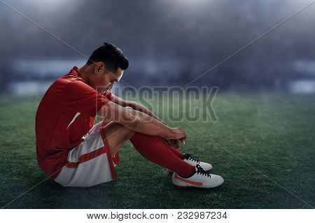 Asian Soccer Player Lose Sitting On The Field