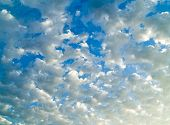 A surreal cloudscape with a bright blue sky in the background. poster