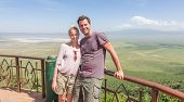 Young couple taking selfie photo in safari clothes on observation platformof beautiful Ngorongoro Conservation Area national park. Safari vacation in Tanzania. poster