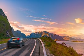Car On Winding Country Road In Norway, Europe, Scandinavia. Auto Travel On Sunset. Blue Sky With Clo