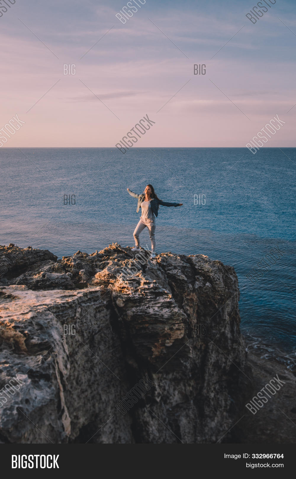 Woman Traveler Standing Near Sea On Top Of Cliff In Summer Mountains And Enjoying View Of Sea And Na