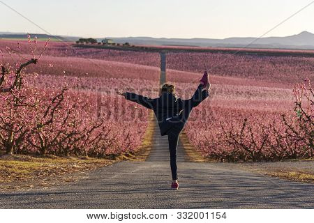 Young Girl Doing A Gymnastic Pirouette With The Pink Sea Peaches In Bloom As Background. Aitona Spri