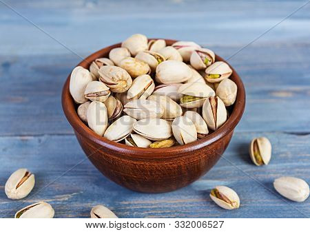 Pistachio Nuts On Wooden Background. Roasted Salted Pistachios.