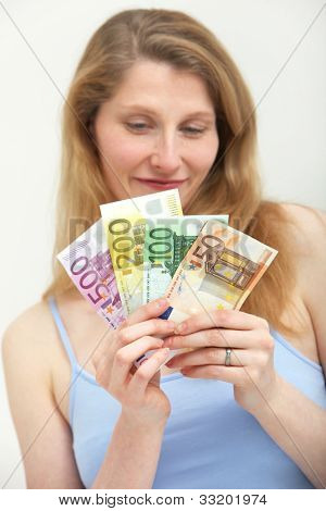 Woman Looking Ruefully At A Handful Of Money