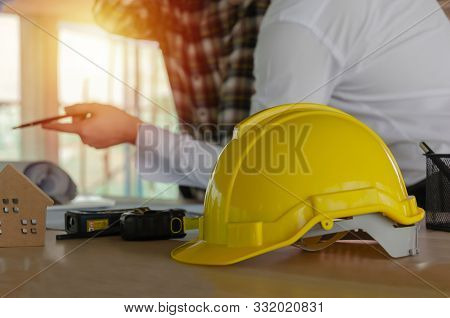 Yellow Safety Helmet On Workplace Desk With Construction Worker Team Meeting And Planning About Buil