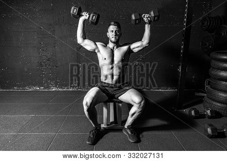 Young Fit Strong Sweaty Man Shoulders Cross Workout Training With Two Dumbbells In The Gym Dark Imag