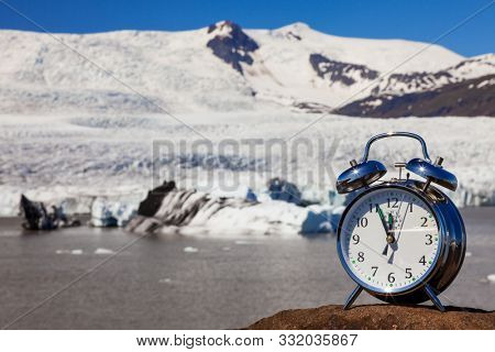 Alarm clock in front of melting glacier and icebergs climate change global warming concept Iceland