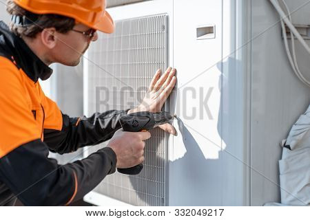 Professional Workman In Protective Clothing Installing Or Reparing Outdoor Unit Of The Air Condition