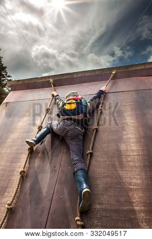 Young Boy In Wellys Climbing Up A Wall With Ropes