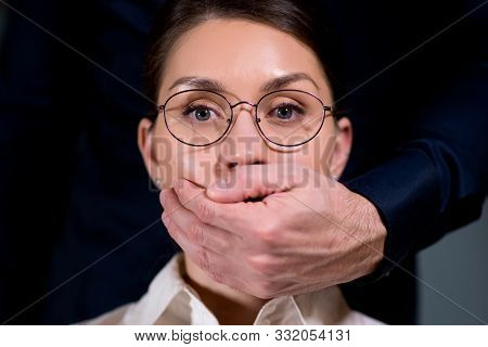 A Man Stands Behind The Girl And Covers Her Mouth With His Hand, Close Up