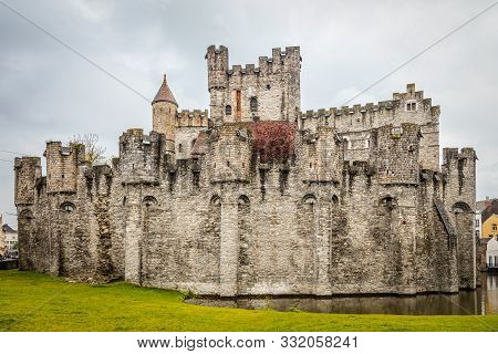 Fortified Walls And Towers Of Gravensteen Medieval Castle With Moat In The Foreground, Ghent East Fl