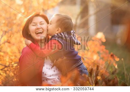 Happy Mother Embracing Little Son In Autumn Garden Or Park. Child Is Kissing Mom, Woman Is Laughing.