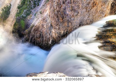 Close Up Of The Brink Of Lower Falls At Yellowstone National Park Showing Rushing Waters From The Ye