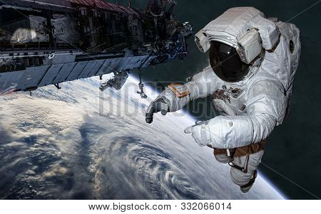 Astronaut And Iss In Orbit Of Earth. Solar System. Science Fiction. Elements Of This Image Furnished