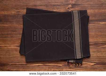Dark brown kitchen towels or napkins on rustic wooden table top. Mock up for design. Top view