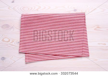 Kitchen towel or napkin on white wooden table top. Mock up for design. Top view