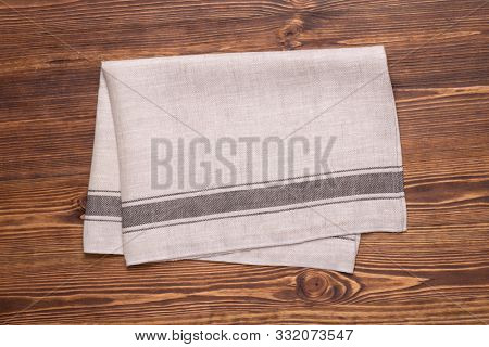 Kitchen towel or napkin on brown rustic wooden table top. Mock up for design. Top view
