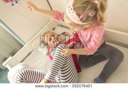 Happy Siblings Lying On Bed At Home And Playing