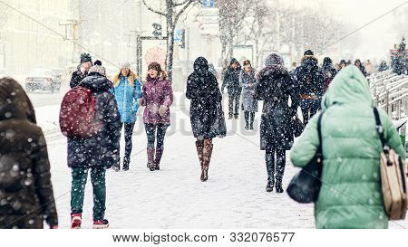 Winter City Sidewalk. Rear View Of People Walking Along An Icy Snowy Pavement. City Dwellers In The