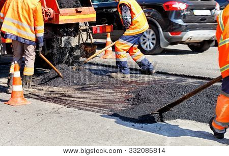The Group Of Road Workers Updates Part Of The Road With Fresh Asphalt, Using Shovels, And Levels It