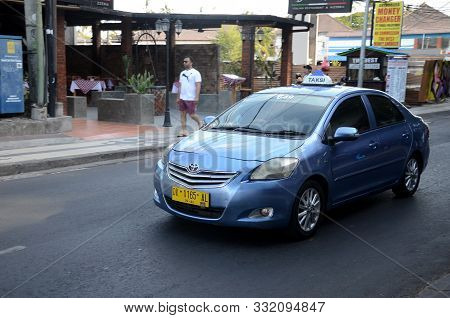 Bali, Indonesia- 18 Oct, 2019: Bali Taxi Travelling On The Street Of Bali. There Are Many Different