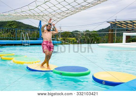 Pattaya, Thailand, August, 3, 2019, Ramayana Waterpark. Man In Activity Pool Overcomes An Obstacle C