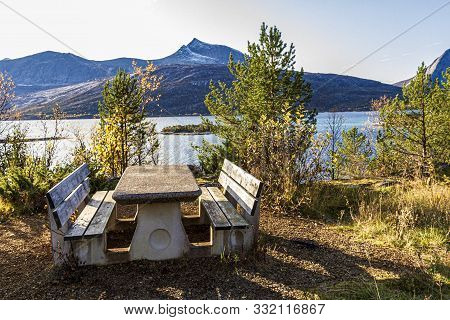 Wooden Picnic Table With A Norway Fjord In Its Background