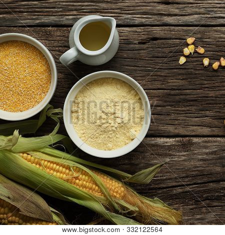 Corn Oil, Polenta Corn Grits, Corn Flour In A Porcelain Bowl On A Wooden Table. Ears Of Corn And Sli