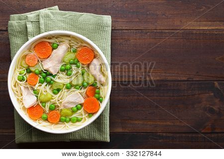 Fresh Homemade Chicken Noodle Soup With Carrot, Peas And Celery In White Soup Bowl, Photographed Ove
