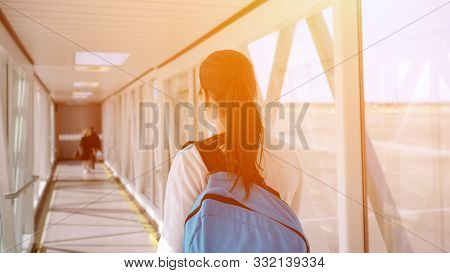 Happy Young Woman With Backpack Is Going On Telescopic Gangway To The Airplane, Sunlight