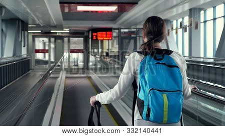 Young Woman Traveller On Escalator With Backpack And Suitcase In Airport Terminal. She Is Going To T