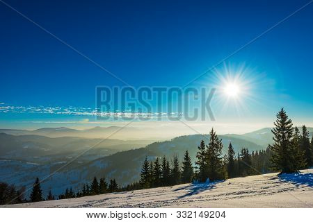 Beautiful Panorama Of A Snowy Slope With A Forest And A View Of The Snowy Mountain Ranges Covered In