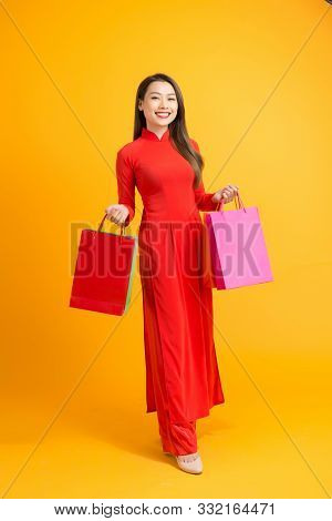 Vietnamese Woman Wearing Traditional Ao Dai Clothes And Holding Shopping Bags In Tet Festival On Whi
