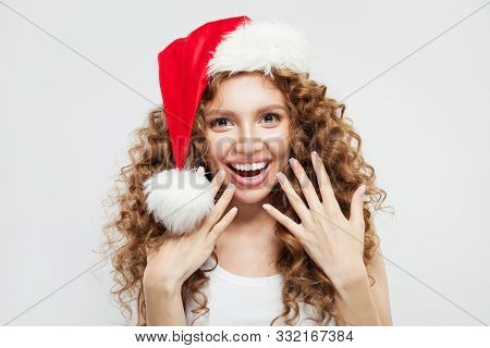 Happy Excited Surprised Young Woman In Santa Hat Smiling. Christmas And New Year Party Portrait