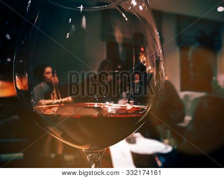 Focus In Foreground Of A Glass Of Red Wine - Background Out Of Focus Of A Family In A Warm Indoor En