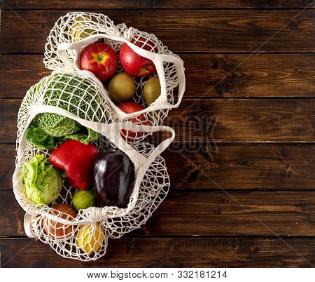 Vegetables And Fruits In Net Bags On Dark Rustic Background