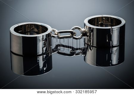 Gold Handcuffs Lie On A Gray Metal Mirror Surface Opened For One Hand. Concept Tempting Offer And Da