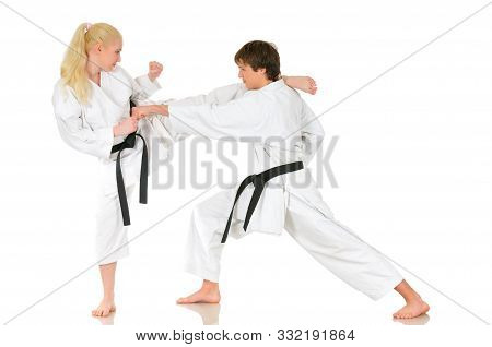 Beautiful Young Girl And A Young Cheeky Guy Karate Are Engaged In Training In Kimono On A White Back