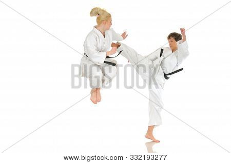 Cute Blonde Girl And A Young Cheeky Guy Karate Are Engaged In Training In A Kimono On A White Backgr